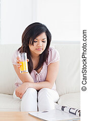 Woman sitting on a sofa while holding a glass of juice