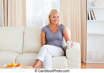 Woman sitting on a sofa with a cup of tea