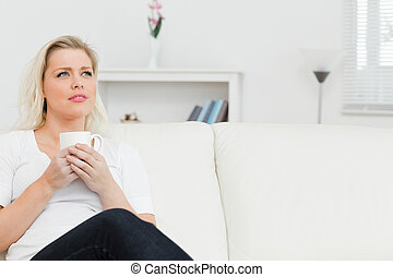 Woman sitting on a sofa with cup in her hands