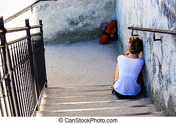 woman sitting on a staircase, symbol photo for loneliness, ...
