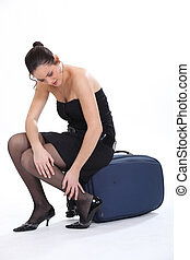 Woman sitting on a suitcase rubbing her ankle