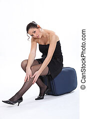 Woman sitting on a suitcase smoothing her stockings