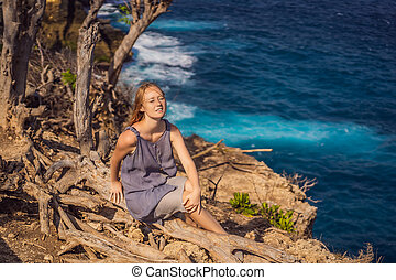Woman sitting on a tree against the background of the sea Angel's Billabong in Nusa Penida, Bali, Indonesia. Bali Travel Concept