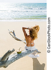 Woman sitting on a tree trunk at the tropical beach