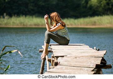 Woman sitting on a wooden bridge