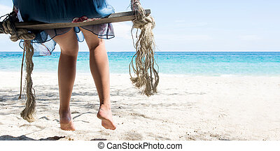 Woman sitting on a wooden swing on the beach