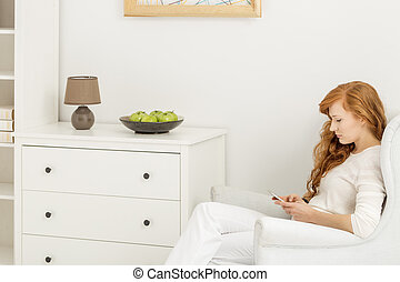 Woman sitting on an armchair in bright room