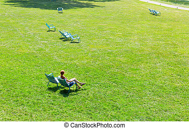 Woman sitting on armchair in the middle of meadow.