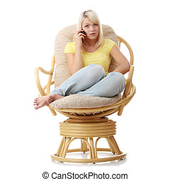 Woman sitting on armchair with cell phone