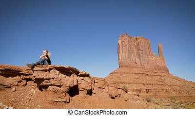 woman sitting on arock with camera enjoying the landscape in Arizona.