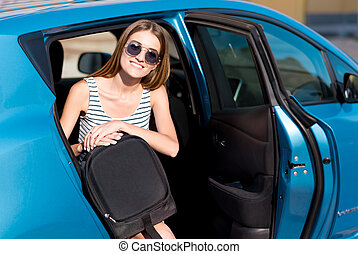 Woman sitting on back seat of car