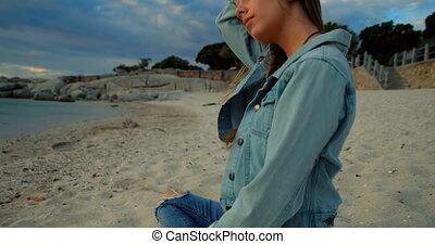 Woman sitting on beach 4k