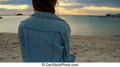Woman sitting on beach 4k - Rear view of woman sitting on...