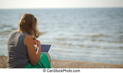 Woman sitting on beach by the sea with touch pad