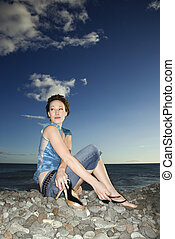 Woman sitting on beach.