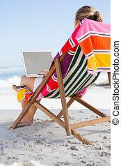 Woman sitting on beach in deck chai