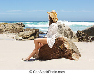 Woman sitting on beach looking at the sea