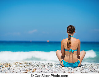Woman sitting on beach. Rear view