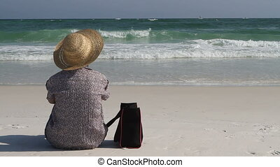 Woman Sitting On Beach With Bag