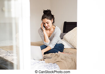 Woman sitting on bed, making phone call. Home office.