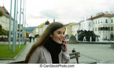 Woman sitting on bench in old town making phone call