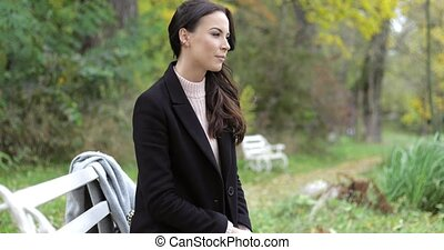 Woman sitting on bench in park - Beautiful woman in black...