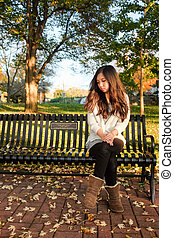 lonely young woman sitting on a steel bench