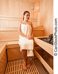 Woman sitting on bench next to sauna oven