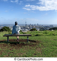 Woman sitting on bench will looking at skyline of Auckland
