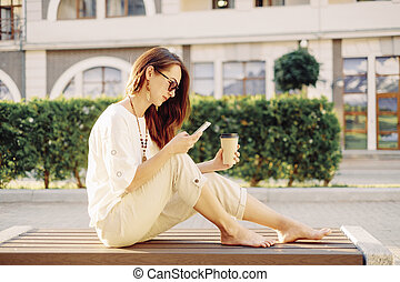 Woman sitting on bench with cup of coffee and using mobile phone.