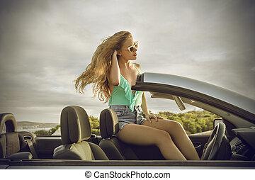 Woman sitting on car