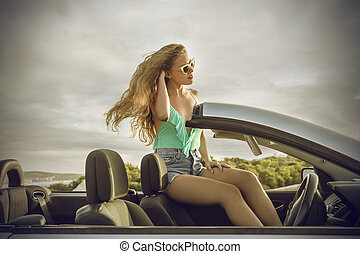 Woman sitting on car