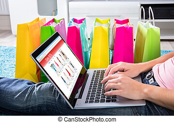 Woman Sitting On Carpet Using Laptop To Shop Online