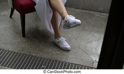 Woman sitting on chair in wedding dress and sneakers