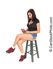 Woman sitting on chair, playing with her game