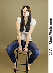 Woman sitting on chair smiling in studio