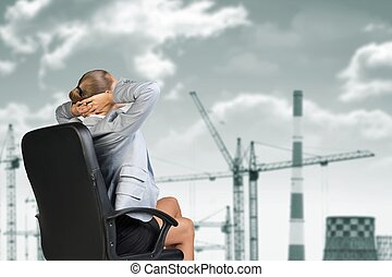 Woman sitting on chair. Tower crane, chimneys and clouds as backdrop