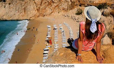 Woman Sitting On Cliff above sand beach
