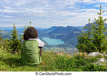 woman sitting on cliff and looking at landscape