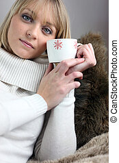 Woman sitting on cosy sofa with mug of coffee