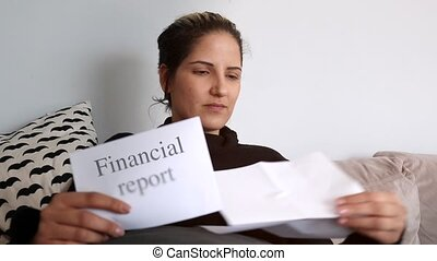 Woman sitting on couch reading financial reports