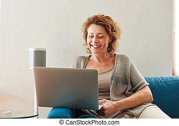 Woman sitting on couch with laptop at home