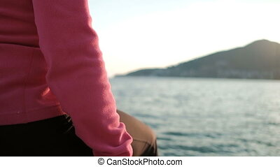 woman sitting on deck by water, looking into distance. Shooting back