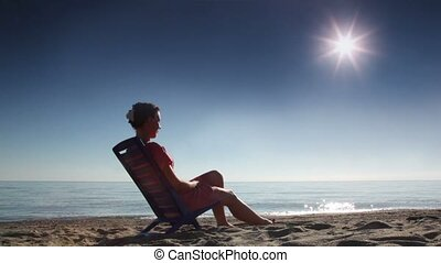 Woman sitting on deckchair and tans, on beach at sunny day,...