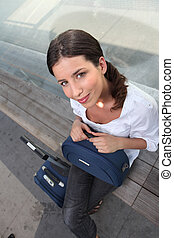 Woman sitting on dock with luggage