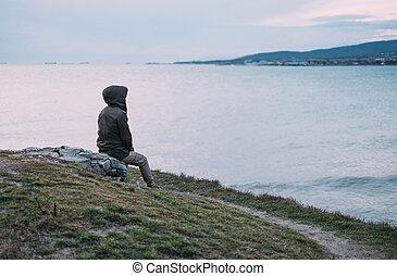 Woman sitting on edge coast