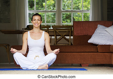 Woman sitting on floor at home in yoga position