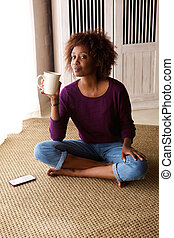 Woman sitting on floor at home with coffee and mobile phone