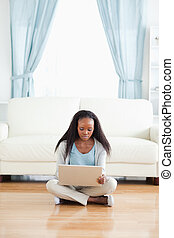 Woman sitting on floor with her laptop
