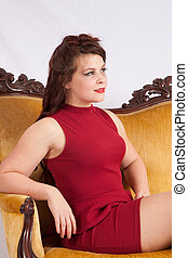 Pretty woman in red dress sitting on a gold couch